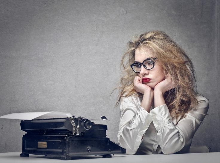 beautiful journalist looks typewriter